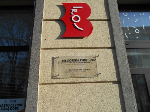 Czytelnia Pod Sowami logo biblioteki oraz tabliczka z nazwą placówki znajdujące się przy wejściu głównym