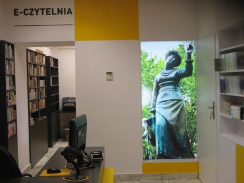 """Czytelnia Naukowa nr 16 widok w środku na wejście do sali komputerowej oraz na duże zdjęcie pomnika """"Dziewczyna z Dzbanem"""" (żoliborska Alina)"""