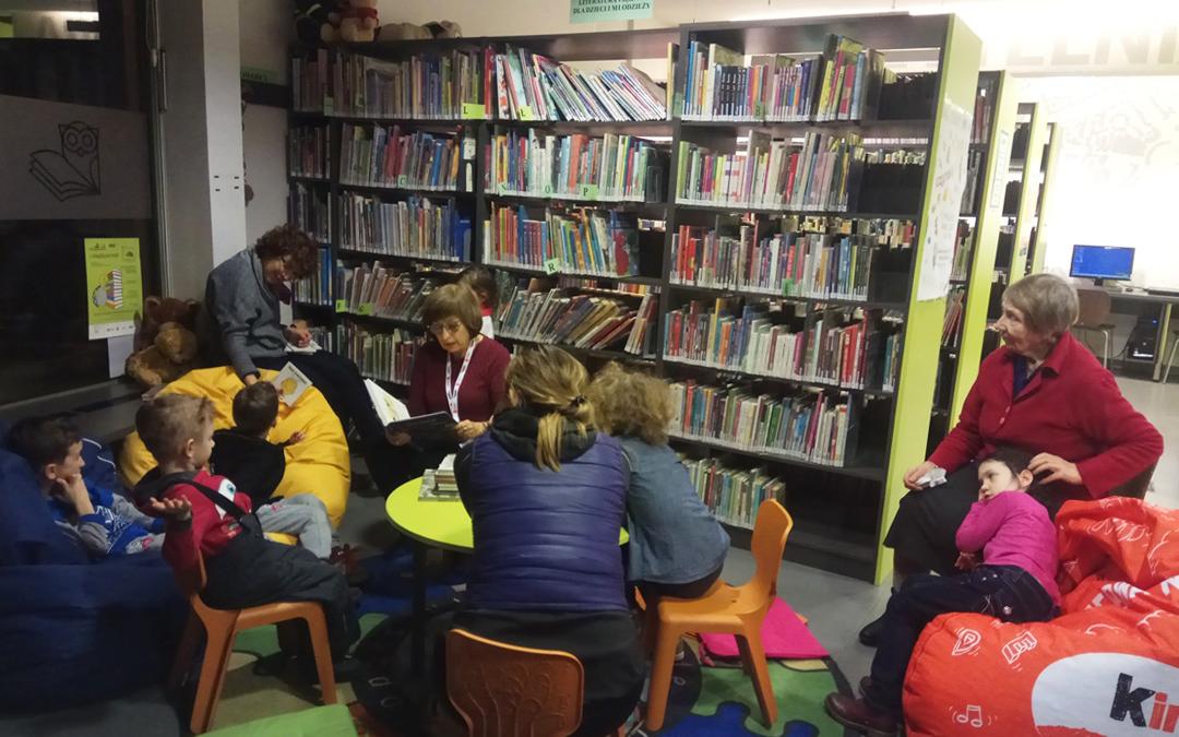 Wolontariuszka w bibliotece przy ul. Mickiewicza 65 czyta dzieciom bajki