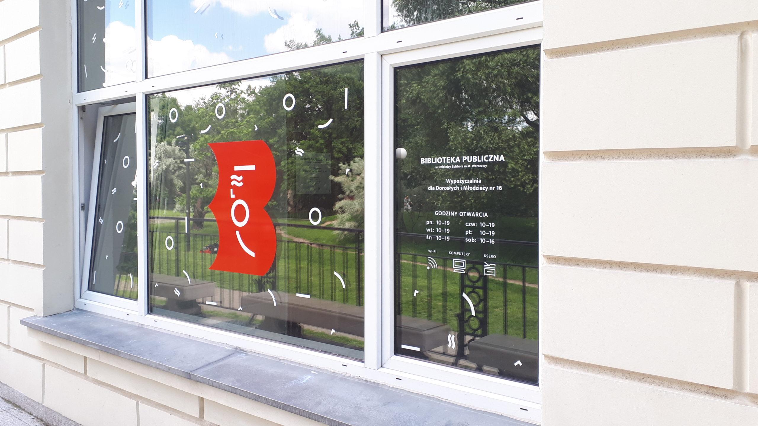 Wypożyczalnia nr 16 widok z zewnątrz na logo biblioteki naklejone na oknie