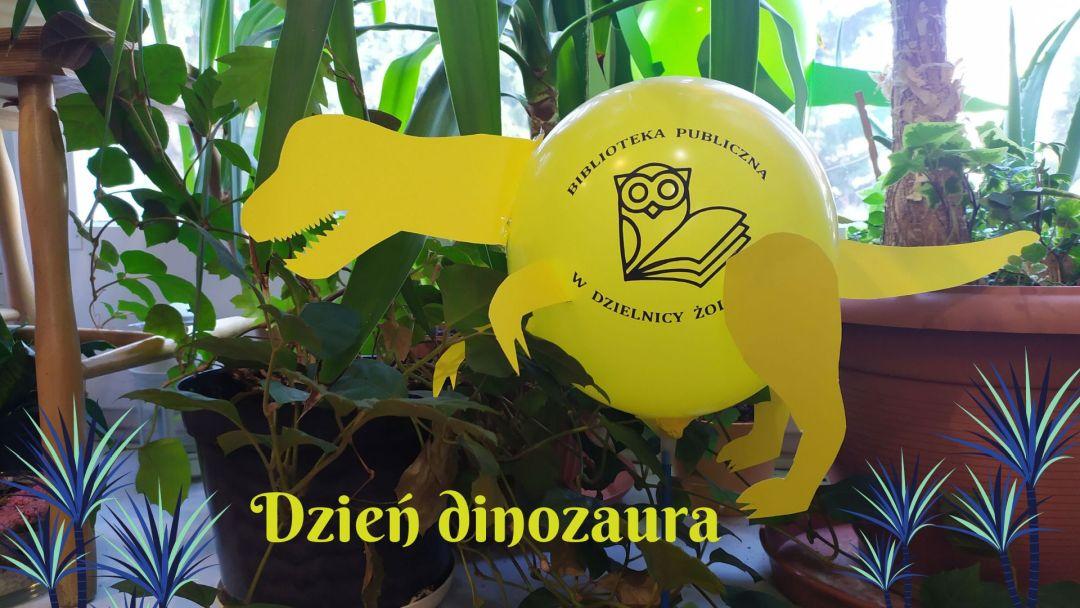 Grafika wyróżniająca. Predstwia dinozaura-zabawkę na tle roślin