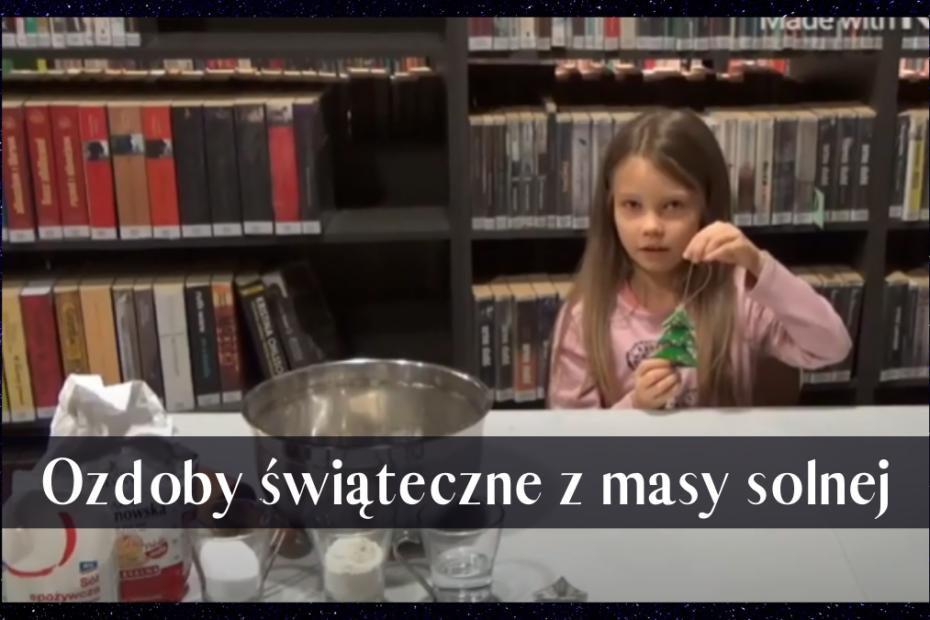 Kadr z filmu instruktażowego o ozdobach świątecznych z masy solnej. Na zdjęciu dziewczynka prezentuję ozdobę, którą następnie wykona podczas filmu
