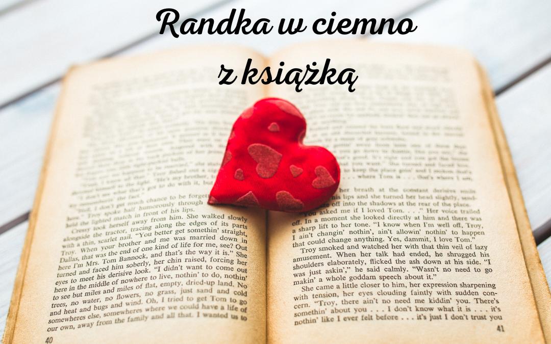 Obrazek wyróżniający do zabawy Randka w Ciemno z Książką. Na zdjęciu jest otwarta książka i leżące na niej czerwone serduszko